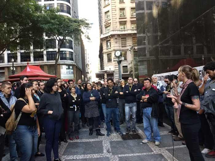 Foto da bancária, representante sindical, Thais Menezes, falando ao microfone com outros trabalhadores em volta