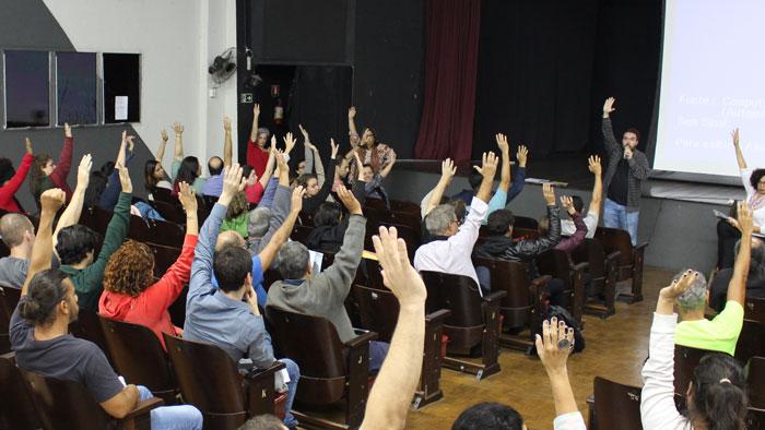 Foto da votação. Todos de braço levantado aprovando a greve.